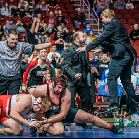 Kaden Sutton, the moment he won his final match at State. The coaches, cheerleaders and crowd behind, show their excitement.