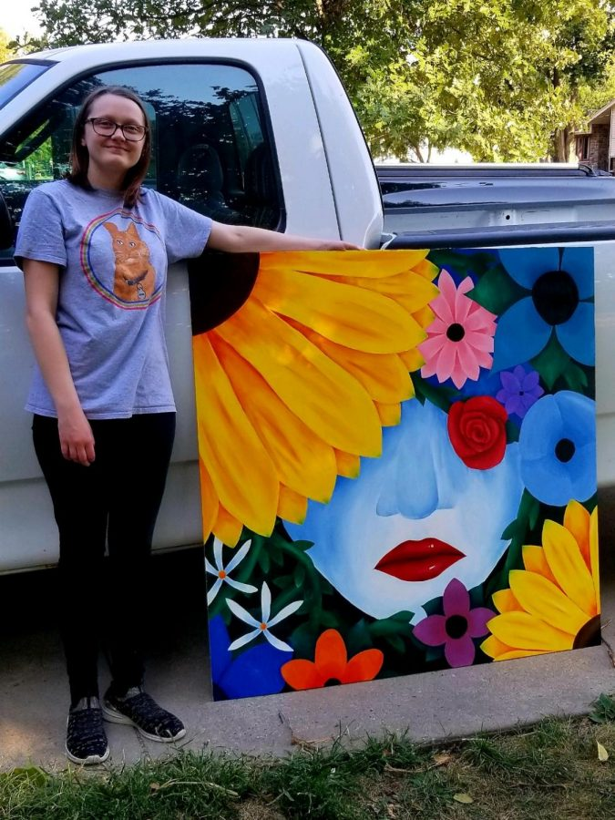 Junior, Madden Strand poses with her mural.