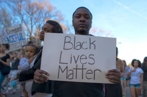 "A man holds up a ""Black Lives Matter"" sign at a protest."