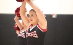 During this half-time show, Senior Sarah Moews smiles proudly, demonstrating her skills in the pom routine.