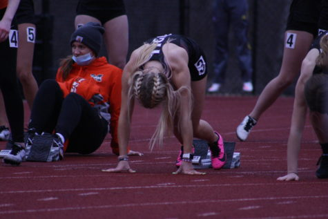 "Lining up for the 100m dash, Junior Olivia Tollari gears up for her race. Tollari said, ""the brisk weather pushed me to run even faster."" She placed second in the race, and earned ADM points in the meet."
